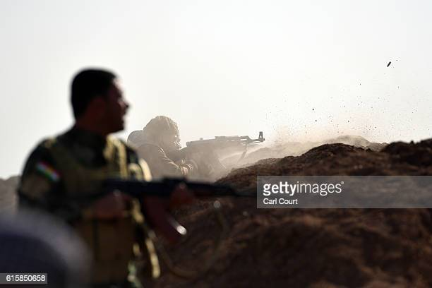 Kurdish peshmerga soldier fires his rifle at an ISIS position during an assault to recapture the village of Tiskharab on October 20, 2016 near Mosul,...