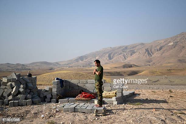 Kurdish peshmerga soldier prays on a front line position as forces continue the battle to retake Mosul, on October 19, 2016 in Bashiqa, near Mosul in...