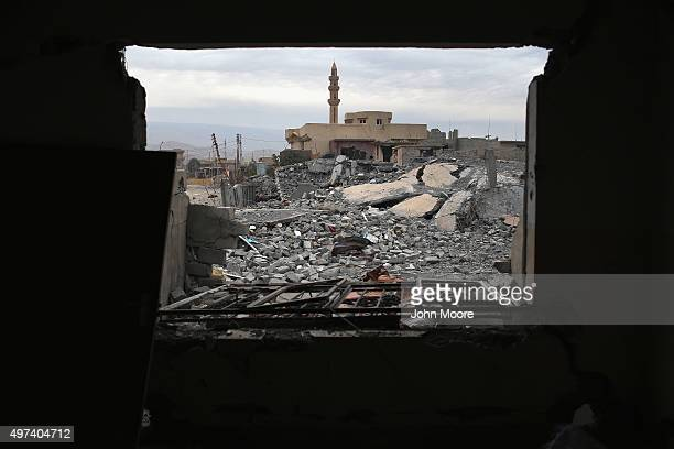 Kurdish Peshmerga soldier searches for weapons in the rubble of an airstrike near a mosque on November 16 2015 in Sinjar Iraq Kurdish forces with the...
