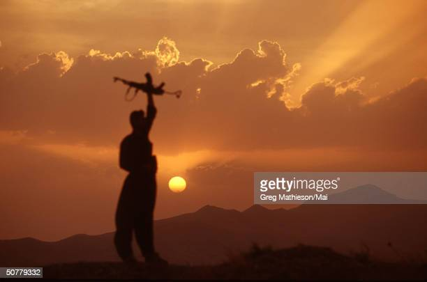 Kurdish peshmerga soldier standing atop a mountain overlooking Iraqi military postions, but within the protected area patroled by the US lead...