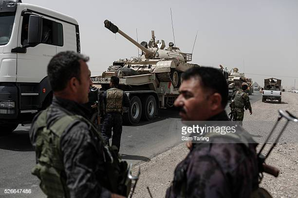 Kurdish Peshmerga soldiers look on as a tank that was abandoned by the Iraqi army is towed toward Kirkuk in Northern Iraq near the current front line...