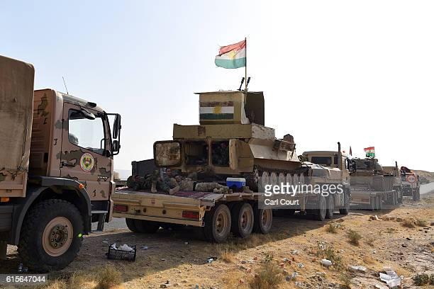 Kurdish peshmerga soldiers relax next to armoured military vehicles near a road to Mosul as forces continue the battle to retake Mosul on October 19...