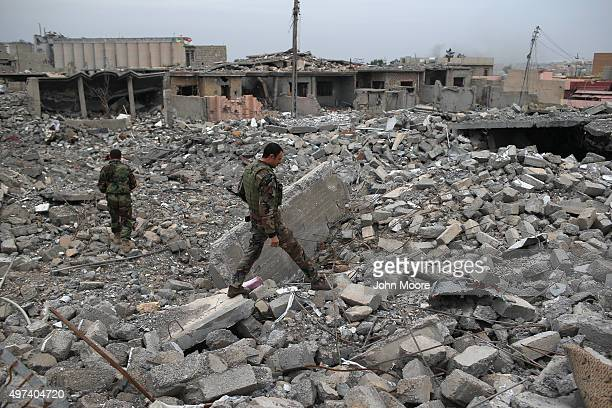 Kurdish Peshmerga soldiers searches for weapons in the rubble of an airstrike on November 16 2015 in Sinjar Iraq Kurdish forces with the aid of...