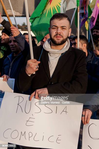 Kurdish protester holds a sign saying 'Russia complicit' during a Kurdish community protest near the Russian Embassy to denounce Russia's complicity...