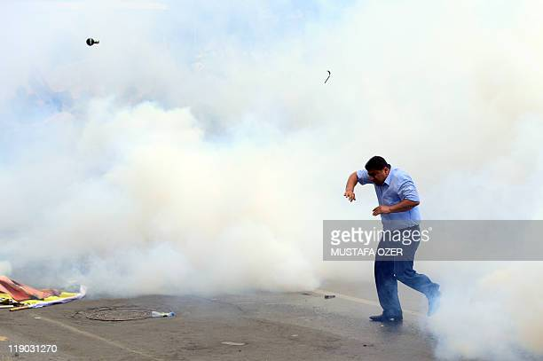 A Kurdish protester runs amidst tear gas smoke during clashes between Kurdish and Turkish leftist groups and riot policemen on June 26 in Istanbul...
