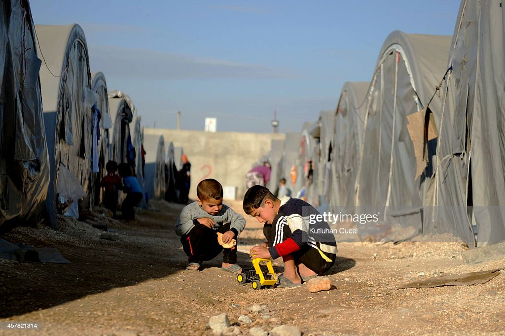 Kurdish refugee boys from the Syrian town of Kobani play with their toys in a camp in the southeastern town of Suruc, Sanliurfa province on October 25, 2014. The Syrian town of Kobani has yet again seen fierce fighting between Islamic State and Syrian Kurdish forces. Since mid-September, more than 200,000 people from Kobani have fled into Turkey.