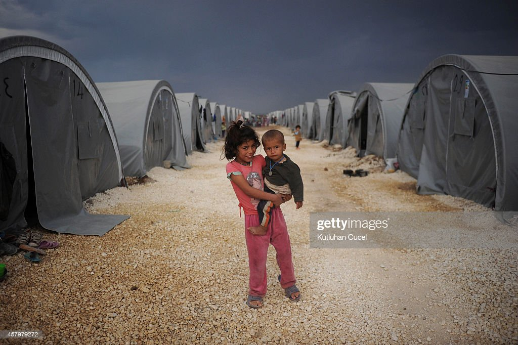 Kurdish refugee children from the Syrian town of Kobani look on near makeshift tents in a camp in the southeastern town of Suruc, Sanliurfa province October 28, 2014. Kurdish fighters, supported by US-led air strikes, have fended off the Islamic State militants offensive into the besieged Syrian border town of Kobani for the last 44 days but remain ill equipped and short on ammunition.