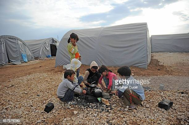 Kurdish refugee children from the Syrian town of Kobani prepare tea near makeshift tents in a camp in the southeastern town of Suruc Sanliurfa...