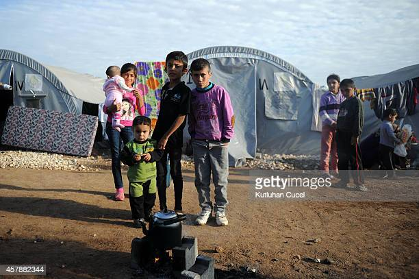 Kurdish refugee children prepare tea in front of their family tent in a refugee camp on October 26 2014 in the southeastern town of Suruc TurkeyThe...