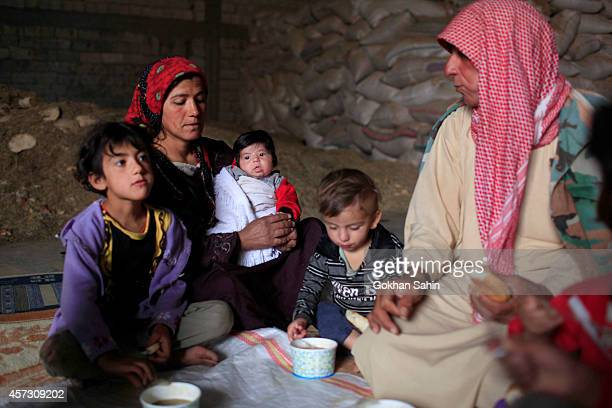 A Kurdish refugee family eats lunch in a temporary shelter in a refugee camp on October 16 2014 in the southeastern town of Suruc Turkey According to...