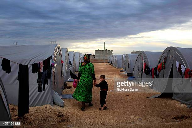 Kurdish refugee mother and son from the Syrian town of Kobani walk beside their tent in a camp in the southeastern town of Suruc on the...