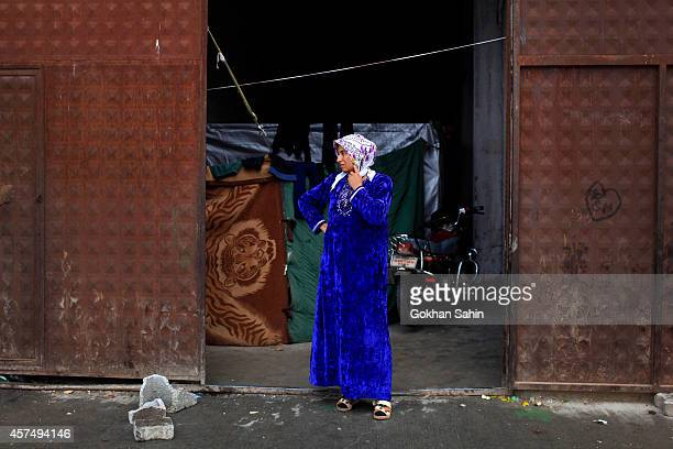 A Kurdish refugee woman from the Syrian town of Kobani stands in front of the entrance to her temporary home in a camp in the southeastern town of...