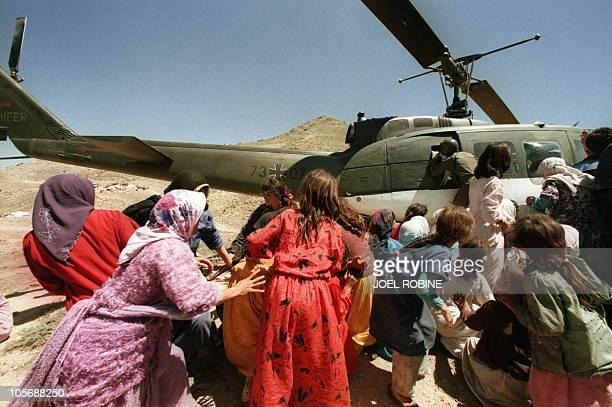Kurdish refugees scramble 28 April 1991 to board a German Air Force helicopter as they leave the mountains of Qasrok northern Iraq for an undisclosed...
