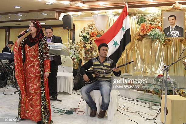 A Kurdish singer performs during a celebration of the Noruz spring festival at a restaurant in Damascus decorated with a Syrian flag and a picture of...