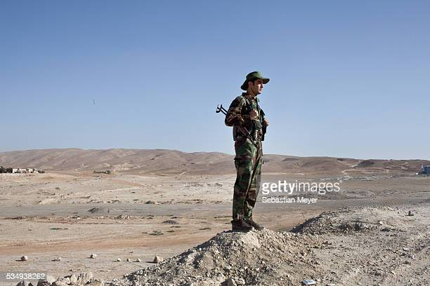 Kurdish soldier also known as 'peshmerga' stands watch near the frontline on the outskirts of the town of Makhmor 35 miles south of Erbil the capital...