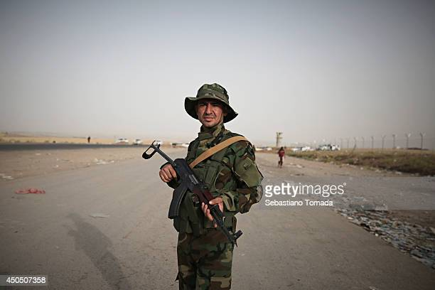 Kurdish soldier at one of the checkpoints that have been recently opened to refugees fleeing from Iraq after ISIS militants have overrun and taken...