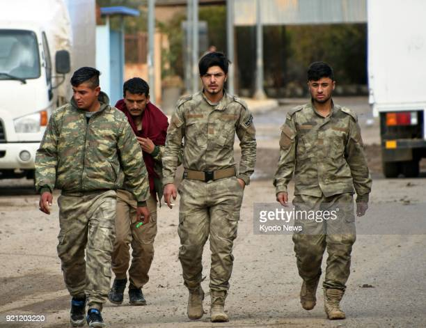Kurdish soldiers who belong to the Syrian Democratic Forces walk in the alOmar oilfield in Deir ezZor eastern Syria on Feb 18 2018 ==Kyodo