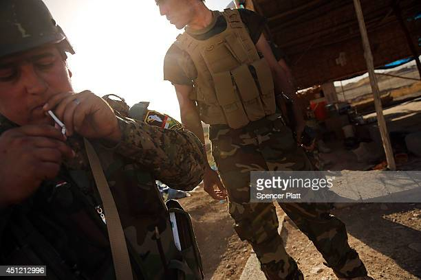 Kurdish soldiers with the Peshmerga keep guard near the frontline with Sunni militants on the outskirts of Kirkuk, an oil-rich Iraqi city on June 25,...