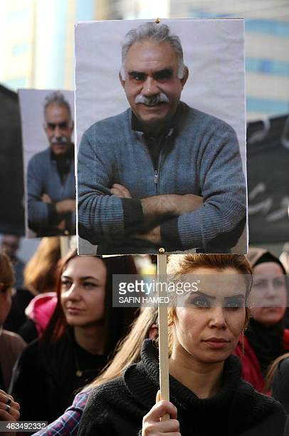 A Kurdish supporter of the Kurdistan Workers Party holds a placard with a portrait of PKK's leader Abdullah Ocalan during a demonstration calling for...