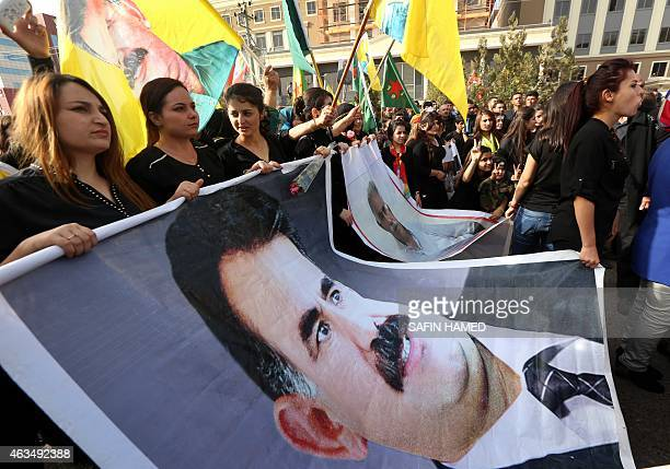 Kurdish supporters of the Kurdistan Workers Party hold giant posters whowing portraits of PKK's leader Abdullah Ocalan during a demonstration calling...