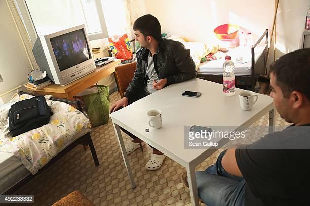Kurdish Syrian asylumapplicants Mohamed Ali Hussein and his cousin Sinjar Hussein watch an AlJazeera news broadcast in Arabic in the room they share...