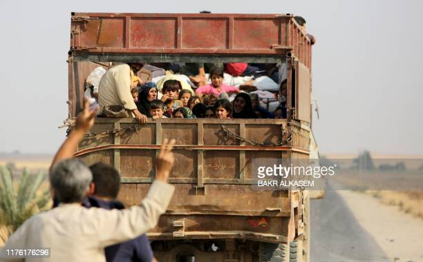 Kurdish Syrian civilians flee the town of Kobane on the Turkish border on October 16, 2019 as Turkey and its allies continue their assault on...