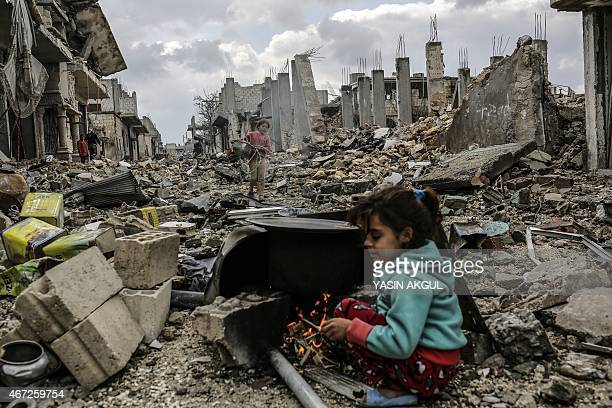 Kurdish Syrian girls are pictured among destroyed buildings in the Syrian Kurdish town of Kobane also known as Ain alArab on March 22 2015 AFP...