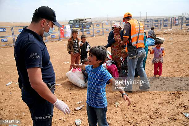 A Kurdish Syrian refugee boy opens his hands for the security check after crossing the TurkishSyrian border near the southeastern town of Suruc on...