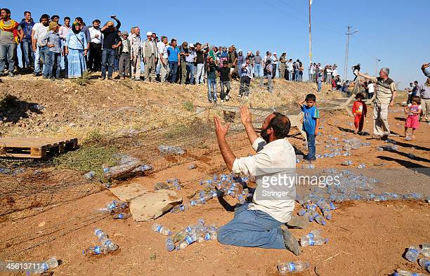 Kurdish Syrian refugees and Turkish protestors pull down a part of the TurkishSyrian border fence near the southeastern town of Suruc in Sanliurfa...