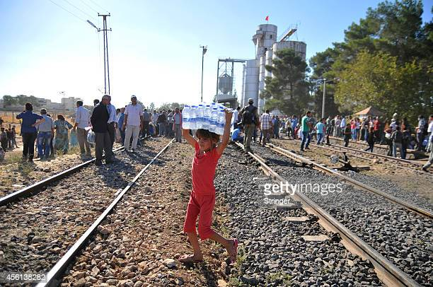 Kurdish Syrian refugees carries a pack of water as Turkish protestors pull down a part of the TurkishSyrian border fence near the southeastern town...