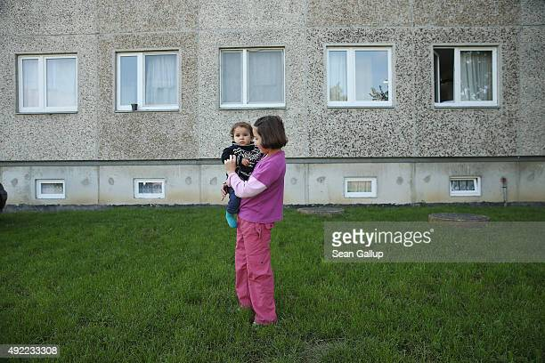 Kurdish Syrian refugees Leila carries her sister Avin in the backyard at the asylumseekers' shelter that is home to them and their family in Vossberg...