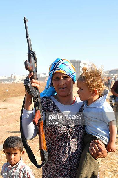 A Kurdish Syrian woman holds a AK47 in the Turkish side of the Syrian border after the refugees and Turkish protestors pull down a part of the...