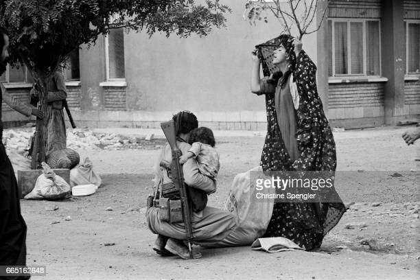 A Kurdish woman adjusts her veil while an armed man holding a child squats to reach something on the ground Family life is difficult as conflicts...
