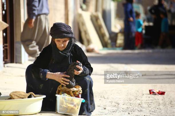 A Kurdish woman holds clothes on a street in Sarpole Zahab in the western Iranian province of Kermanshah on Nov 14 two days after a magnitude...