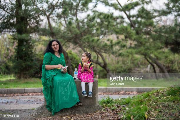Kurdish woman in traditional dress sits with a young girl as they eat during Nowruz celebrations on March 24 2018 in Tokyo Japan Nowruz meaning 'new...