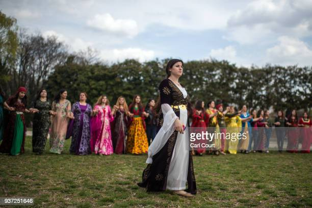 Kurdish woman in traditional dress walks past friends as they dance during Nowruz celebrations on March 24 2018 in Tokyo Japan Nowruz meaning 'new...