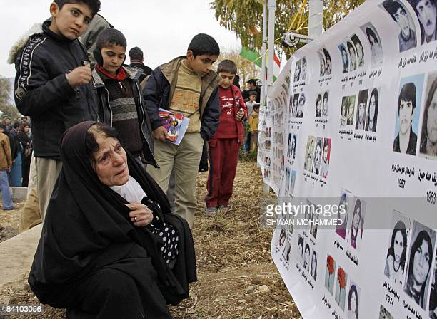 Kurdish woman looks at pictures of victims of the 1988 Halabja gas attacks during a memorial in the grave-yard of the northern Iraqi Kurdish city of...