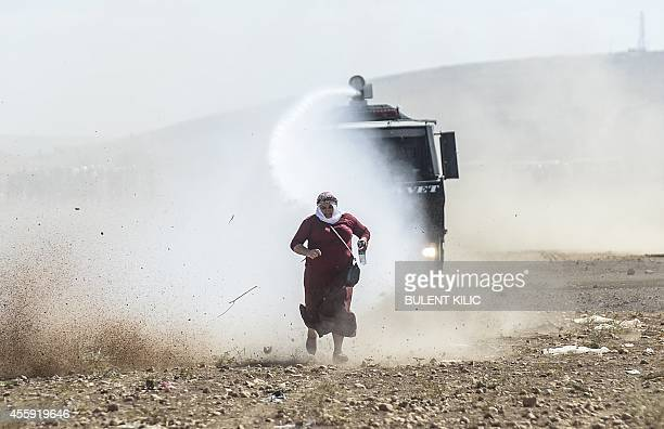 Kurdish woman runs away from a water cannon during clashes with Turkish soldiers near the Syrian border after Turkish authorities temporarily closed...