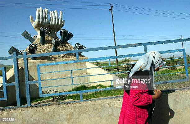 Kurdish woman walks by a memorial to the Iraqi regime's March 16, 1988 gas attack on the Kurdish city of Halabja - which killed 5,000 people - March...