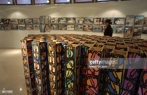 Kurdish woman walks past a sculpture representing 5,000 faces and photos of victims of the March 16, 1988 chemical attacks on Halabja at a museum and...
