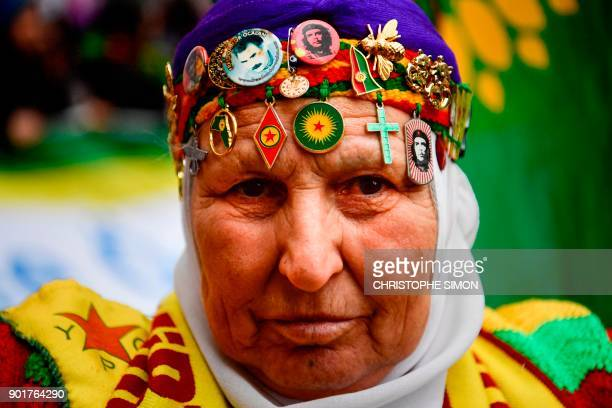 A Kurdish woman wearing Kurdish badges on her head takes part in a demonstration in Paris on January 6 in tribute to the three Kurdish female...