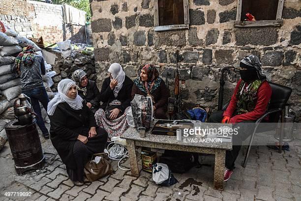 Kurdish women militants sit behind a barricade on November 18 2015 in the Sur district of Diyarbakir Tensions rose when proKurdish MP Leyla Zana...