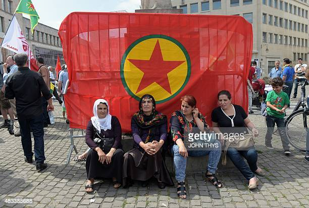 Kurdish women sit in front of a flag of the Kurdistan Workers Party as they attend a demonstration against alleged attacks perpetrated by the Turkish...