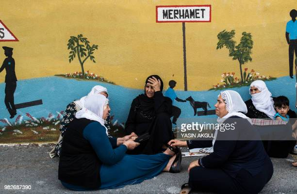 Kurdish women wait outside a polling station during snap twin Turkish presidential and parliamentary elections in Istanbul on June 24 2018 Turks were...