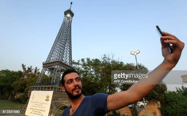A KurdishIraqi uses a cell phone to take a 'selfie' photograph with a model of the Eiffel Tower during its inauguration ceremony in Arbil the capital...