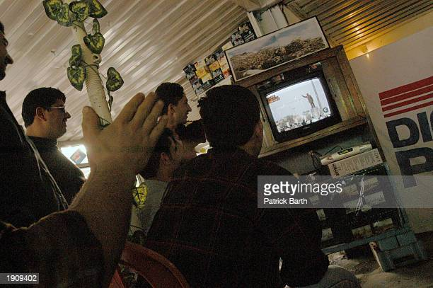 Kurds celebrate while watching the fall of a statue of Saddam Hussien on tv at a roadside restaurant April 9 2003 near Lalesh northern Iraq The...