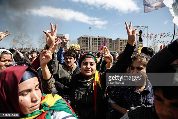 Kurds chant slogans as they flash vsigns during Newroz celebrations on March 21 2015 in Diyarbakir Turkey Thousands of Kurds gather for the Newroz...