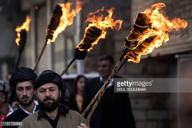 Kurds dressed in traditional outfits carry fire torches as they celebrate Nowruz in the Kurdishcontrolled city of Qamishli in northeastern Syria on...