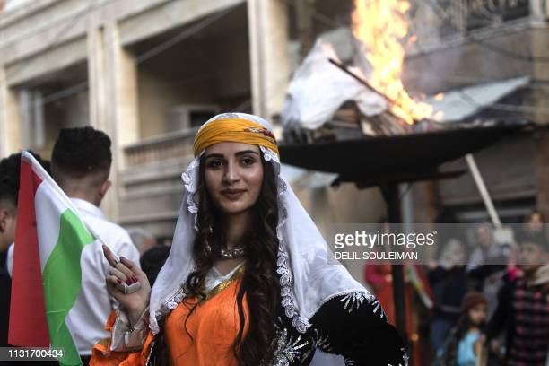 Kurds dressed in traditional outfits celebrate Nowruz in the Kurdishcontrolled city of Qamishli in northeastern Syria on March 20 2019 Nowruz...