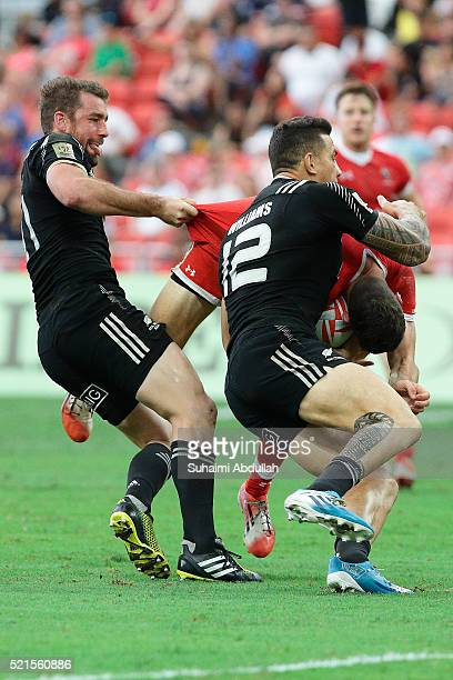 Kurt Baker and Sony Bill Williams of New Zealand tackle Justin Douglas of Canada during the 2016 Singapore Sevens at National Stadium on April 16...